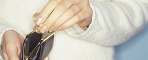 Woman taking coins from purse, close-up of hands, thinking about recent survey from Credit Karma that found nearly 1 in 3 women is discouraged about her finances.