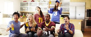 Friends watching a game together, not worried about tax on sports betting.
