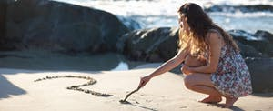 Young woman, frustrated by unanswered tax questions, draws a question mark in the sand on the beach.