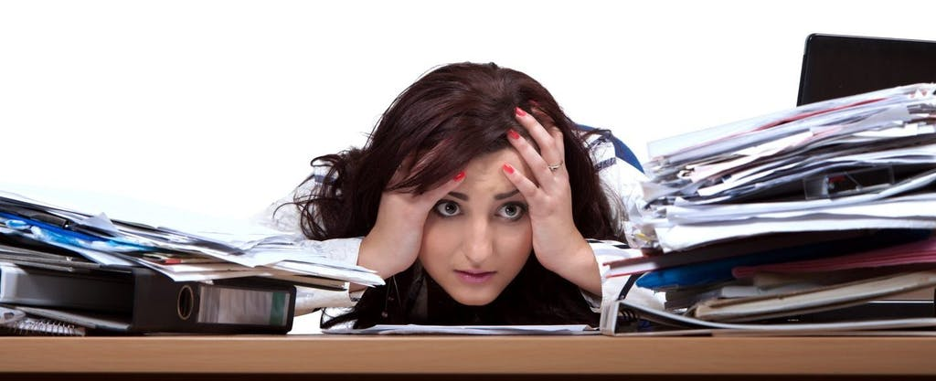 Young hispanic woman, leaning her head on desk in frustration, trying to decide how long to keep tax records.