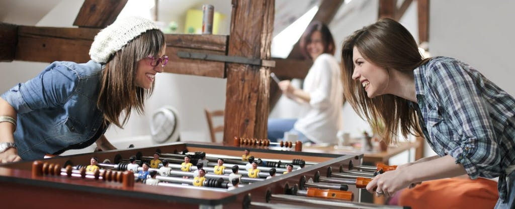 Two young female office workers happily enjoying a fringe benefit of their workplace: a foosball table.