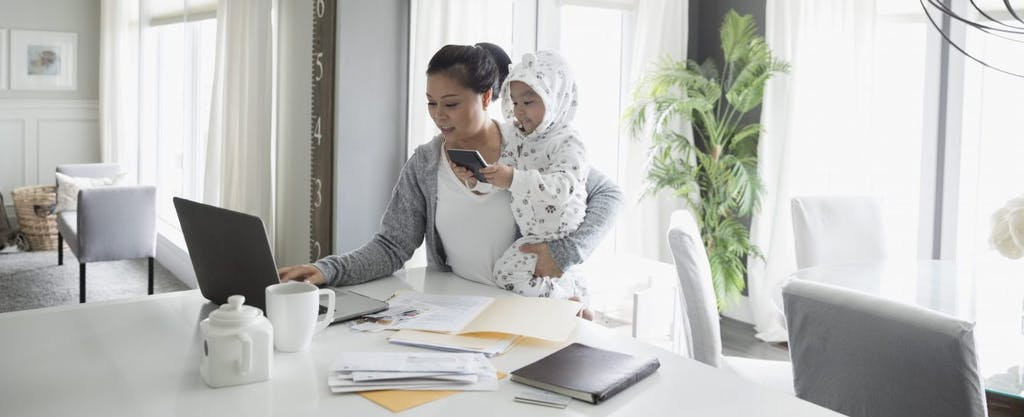 Young Asian mother holding baby and taking the IRS quiz to determine what tax filing status she should use on her federal income tax return.