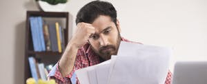 Worried man reading a document at home office