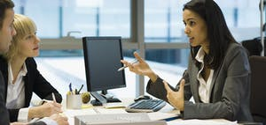 Woman behind desk and computer talking to man and woman