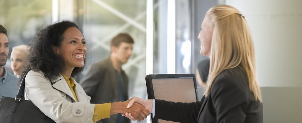 Woman shaking hands with female customer