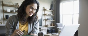 Smiling young woman with credit card and laptop learning about balance transfers in dining room