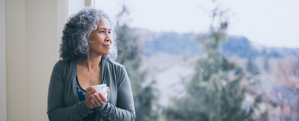 Mature woman looking pensively out her window.