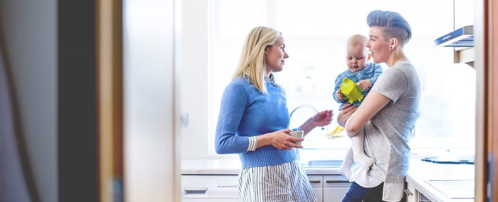Young lesbian couple with baby standing in the kitchen of their home and discussing married filing jointly tax deductions they may be able to take.