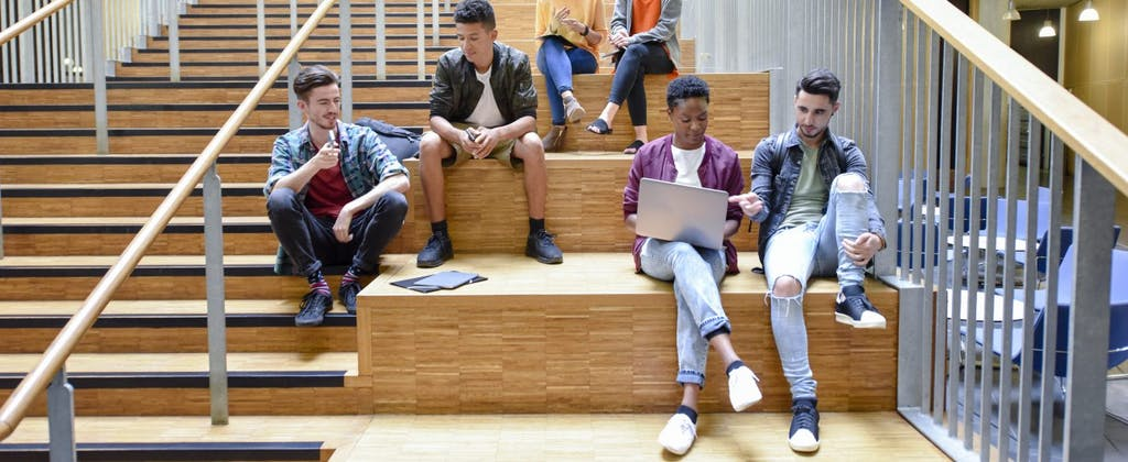 Multi-racial group of college students sitting on stairs and discussing college tax credits that could help them or their parents reduce their federal income tax burden.