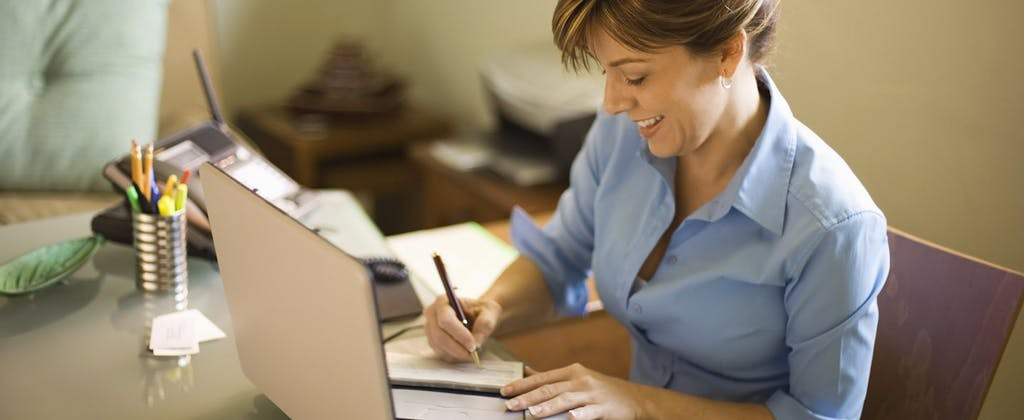 Woman signs a check in her home office.