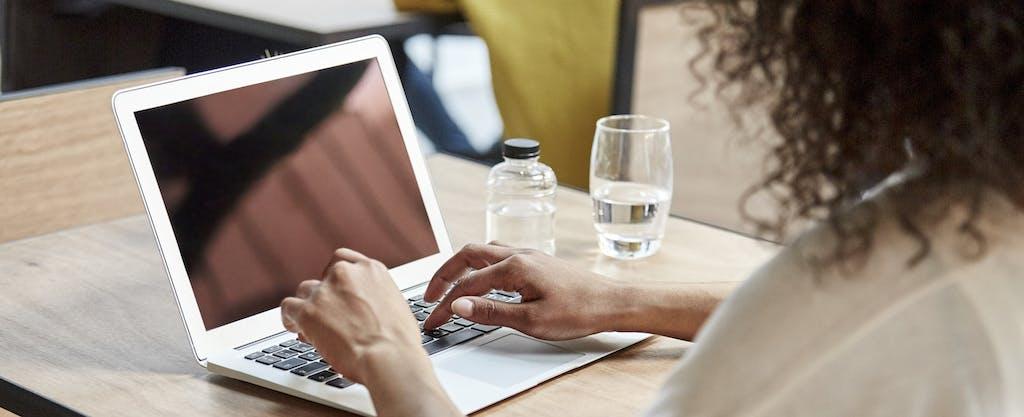 A businesswoman uses a laptop.