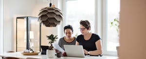 Women discussing financial bills over laptop while sitting at table