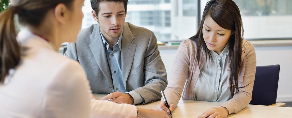 Couple going over documents with person behind desk
