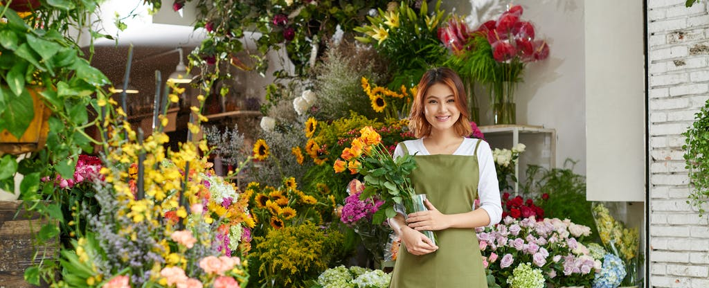 Smiling florist with bouquet of yellow tulips