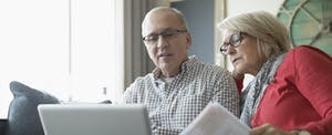 Senior couple looking at paperwork and using laptop