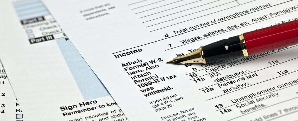 Various tax forms with a pen