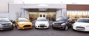 A row of new cars sits in front of a Michigan auto assembly plant.