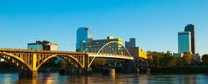 Downtown Little Rock, the capital of Arkansas, is seen in the background with the scenic arch of the Pike Avenue Bridge spanning the Arkansas River in the foreground.