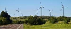 Wind turbines rise above rolling green fields in Oklahoma, making power from the states notorious weather patterns.