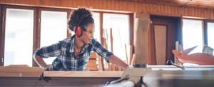 Young African-American woman doing carpentry work and thinking of self-employed tax deductions she may be able to take for her business expenses