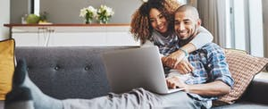 African American couple using laptop to e-file their taxes, smiling confidently.