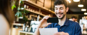 A smiling man takes a picture with his smart phone of a check or paycheck for digital electronic depositing.