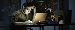 Businessman working late in office, looking worried as he checks his laptop