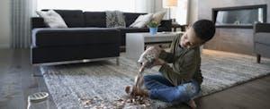 Boy emptying coins from jar onto living room floor
