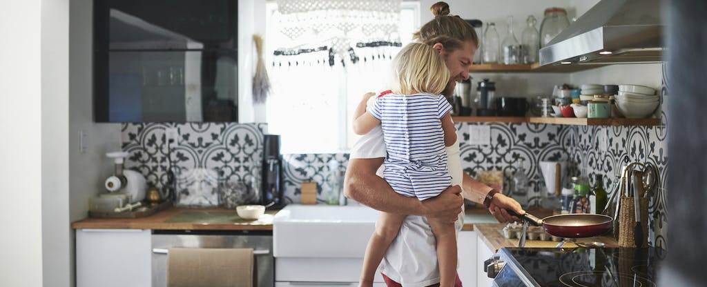 Father holding toddler while cooking food in kitchen