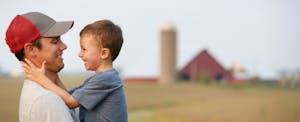 Father and son hug each other on their family farm