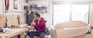 Male carpenter working at laptop in workshop