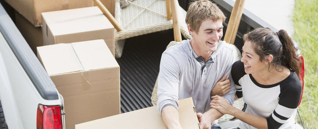 A young man and woman sit in the cab of their moving truck