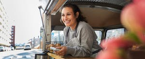 Smiling woman food truck owner in city