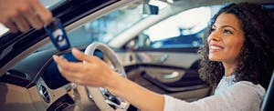 Woman sits in her new car as the deal hands her the keys
