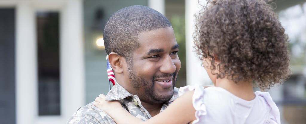 Dad holds his daughter, smiling, upon his return home from military assignment