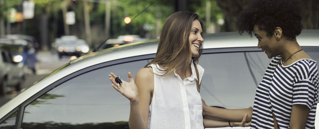 Young woman discussing the fair market value of her car with a male friend