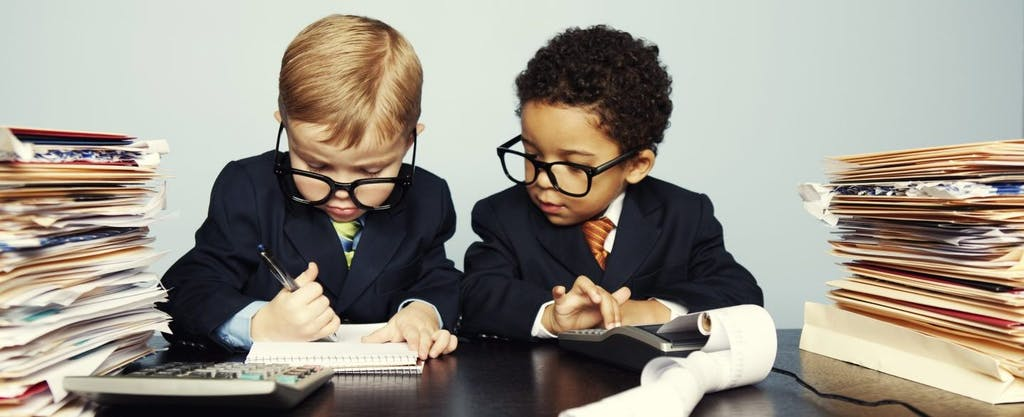 Two toddlers wearing suits and ties, surrounded by stacks of files, work with a calculator, pencil and notepad to determine if they have to pay the kiddie tax.