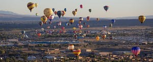 Brightly colored hot air balloons rise above the Albuquerque landscape during the annual festival in New Mexico, where residents must consider if they must file a New Mexico state tax return.