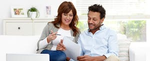 Couple sitting together on sofa calculating expenses