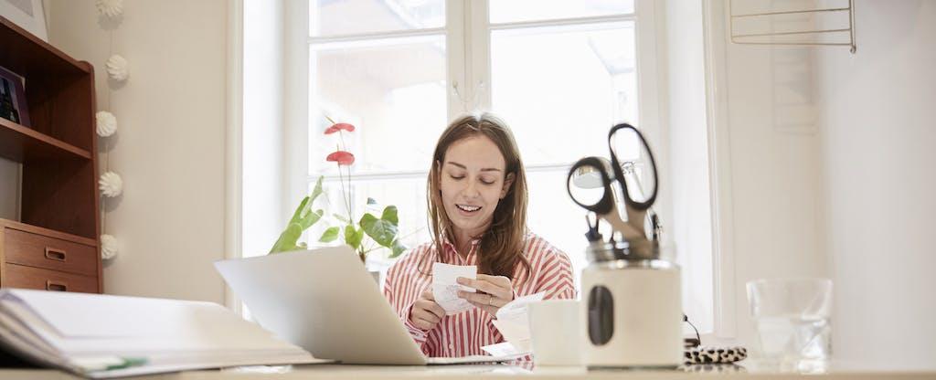 Woman examining receipts at home
