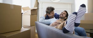 A couple relaxing sofa among moving boxes
