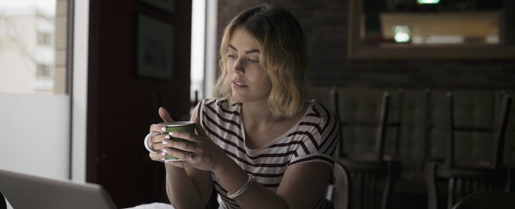 Woman drinking coffee and looking at laptop