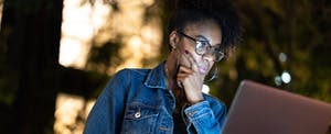 African American woman looks at laptop at night, worried about newly discovered data leak