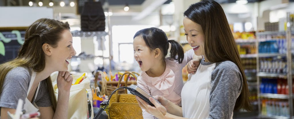 Mother and daughter paying at grocery store checkout