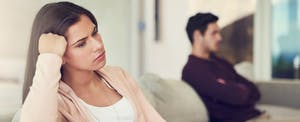 Pensive young couple sitting on couch, wife in the foreground wondering if injured spouse relief can help ensure she doesn't lose all her tax refund due to her husband's past-due tax debt.