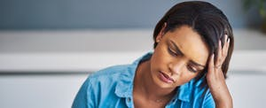 Woman looking stressed with her head in her hand