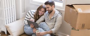 Young couple sitting in room full of boxes, looking at digital tablet
