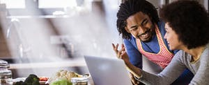 Happy African American couple talking while using laptop in the kitchen