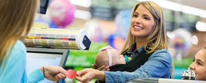 Woman checking out a grocery store and handing her card to the cashier