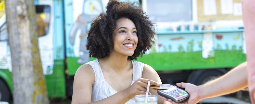 Smiling woman drinking cocktail and using credit card outdoors.